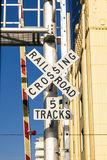 Railroad crossing sign under blue sky Stock Images