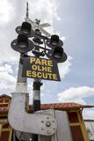 Railroad crossing signal. In the city of Guararema, in the countryside of the Sao Paulo state, Brazil,  Write in portuguese: stop, look, listen. rail road Royalty Free Stock Image