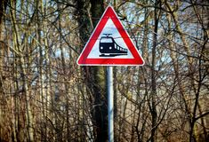 Railroad crossing signal on rural highway. Against vegetation background Stock Images