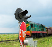 Railroad crossing signs and the approaching train Royalty Free Stock Photography