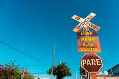 Railroad, crossing, stop, board, blue sky. An old and rusty traffic sign in Minas Gerais Brazil on a sunny day Stock Images