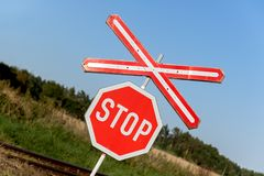 Railroad crossing warning sign. An old railway sign near a tracks. Railway tracks with traffic sign in a rural scene Stock Photo
