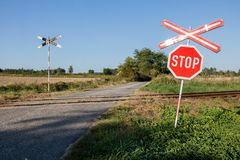 Railroad crossing warning sign. An old railway sign near a tracks. Railway tracks with traffic sign in a rural scene Royalty Free Stock Images