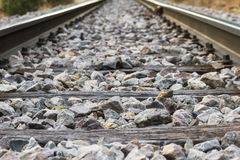Railroad detail with Rails, Sleepers and Paving Stones. Detail of Railroad track with rails, transverse wooden sleepers and paving stones or ballast Stock Images