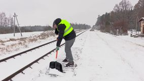 Railroad employee clean snow near the platform stock video