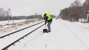 Railroad employee clean snow near railway and walking away stock footage