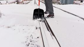 Railroad employee clean snow from the railway crossing stock video