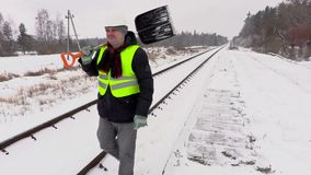 Railroad employee with snow shovel on railway stock footage