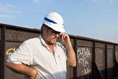 Railroad Engineer on Phone. Railroad engineer using phone at railroad site Stock Images