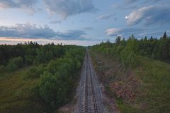 Railroad in Between Forest Under Cloudy Sky Stock Photo