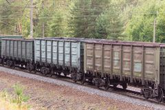Railroad and freight train with rusty railway wagons going along forest. Transportain, cargo concept.  Stock Photography