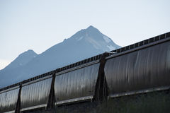 Railroad hopper cars. Freight train with hopper cars beneath mountains stock photos