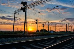 Railroad infrastructure during beautiful sunset and colorful sky, railcar and traffic lights, transportation and industrial concep Royalty Free Stock Images