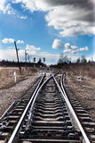 Railroad junction point and the blue sky. Railway bifurcation in north-west of russia in early spring. Blue sky with white clouds. A very cold windy day Stock Photo