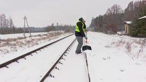 Railroad la neige propre des employés de la plate-forme près du chemin de fer banque de vidéos