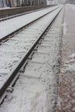 Railroad la perspectiva a lo largo de la estación de la plataforma de la nieve en invierno Fondo del viaje y del viaje trabajador Foto de archivo libre de regalías