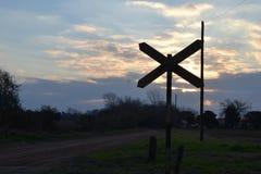 Railroad la señal en contraste con puesta del sol y el oscurecimiento de un cielo semi-nublado y de una calle del país Foto de archivo