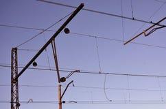 Railroad le linee sopraelevate contro chiaro cielo blu, filo di contatto Linee elettriche ad alta tensione della ferrovia sul bac Fotografie Stock