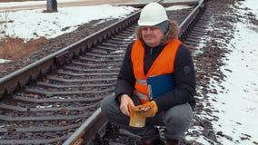 Railroad le travailleur avec des gants et le casque sur le chemin de fer banque de vidéos