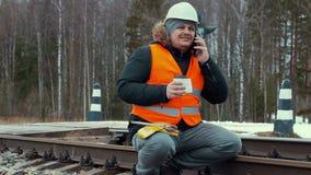 Railroad le travailleur avec du café et des smartphones sur le chemin de fer banque de vidéos