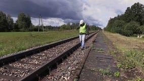 Railroad le travailleur avec la clé réglable marchant près du chemin de fer banque de vidéos