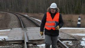 Railroad le travailleur avec la documentation et la clé réglable marchant sur le chemin de fer clips vidéos