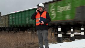Railroad le travailleur parlant au téléphone intelligent près du passage à niveau banque de vidéos