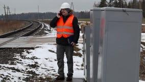 Railroad le travailleur parlant au téléphone portable près de la clôture électrique banque de vidéos