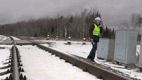 Railroad le travailleur parlant au téléphone près des clôtures électriques banque de vidéos