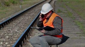 Railroad le travailleur s'asseyant et parlant au téléphone intelligent près du chemin de fer clips vidéos