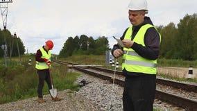 Railroad les ouvriers d'entretien avec la corde et avec la pelle banque de vidéos