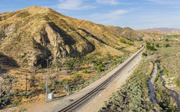 Railroad Line through Desert Canyon. Railroad track line runs alongside a creekbed through the Mojave Desert of California Royalty Free Stock Photo