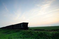 Railroad los coches de grano en las praderas con el cielo azul Fotos de archivo libres de regalías