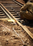 Railroad maintenance. Worker cutting through a railroad track , selective focus Stock Photography