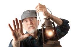 Railroad man holding lantern. Apprehensive railroad man holding a glowing red lantern Stock Image