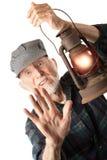 Railroad man holding lantern. Apprehensive railroad man holding a glowing red lantern Stock Images