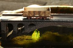 Railroad model on bridge. An old and dirty plastic goods wagon train toy model on bridge model scenery represent the train toy for hobby and collection concept stock images