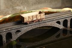 Railroad model on bridge. An old and dirty plastic goods wagon train toy model on bridge model scenery represent the train toy for hobby and collection concept stock photo