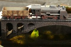 Railroad model on bridge. An old and dirty plastic japanese steam train toy model on bridge model scenery represent the train toy for hobby and collection stock photos