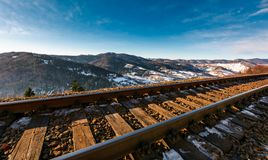 Railroad in mountains with snowy slopes Stock Photo