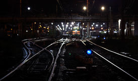 Railroad night scene with blue traffic light. And cargo trains. Selective focus on semaphore Stock Images