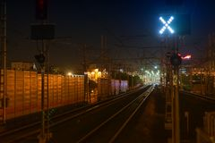Railroad night scene with blue traffic light and railway station tracks, at dusk, golden tones and colors. Industrial. Railroad night scene with blue traffic Stock Image