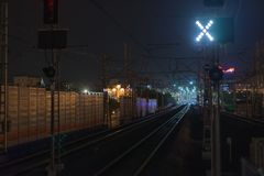 Railroad night scene with blue traffic light and railway station tracks, at dusk, cold tones and colors. Industrial. Railroad night scene with blue traffic light Royalty Free Stock Photography