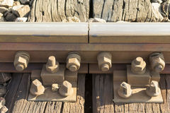 Railroad rail coupling. Steel railroad tracks coupling with reinforced bolts and nuts attached to a wooden beam frame stock photo