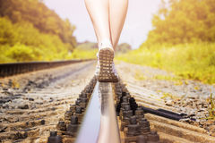Railroad rail feet. Female legs in sneakers on the rail of the railway Stock Photos