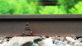 Railroad rail with fixing screw close-up while the train is moving. Summer shot of a railroad rail with fixing screw close-up while the train is moving on it stock footage