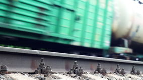 Railroad rail and a train passing on the background. Summer shot of a railroad rail with train passing on the blurred background stock video footage
