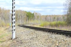 Railroad the railroad embankment of gravel forest sky clouds green grass twist. Of the railway track sleepers Royalty Free Stock Image