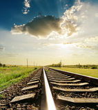 Railroad with reflections under sunset Stock Photo