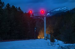 Railroad signals at night with Mountains. A railroad signal stands guard in the Mountains of Montana at dusk Royalty Free Stock Photography